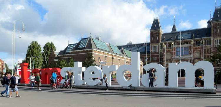 Standing on I AMsterdam letters in Amsterdam