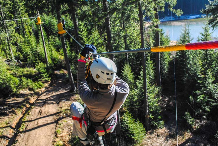sliding on a zip line in an adventure park